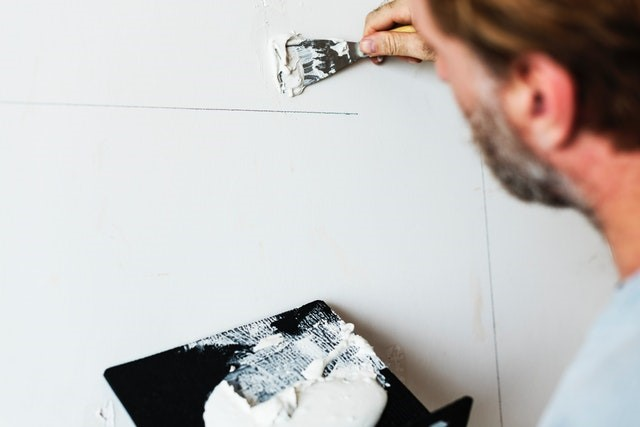 Man holding blackboard with white paint, filling gaps in the wall